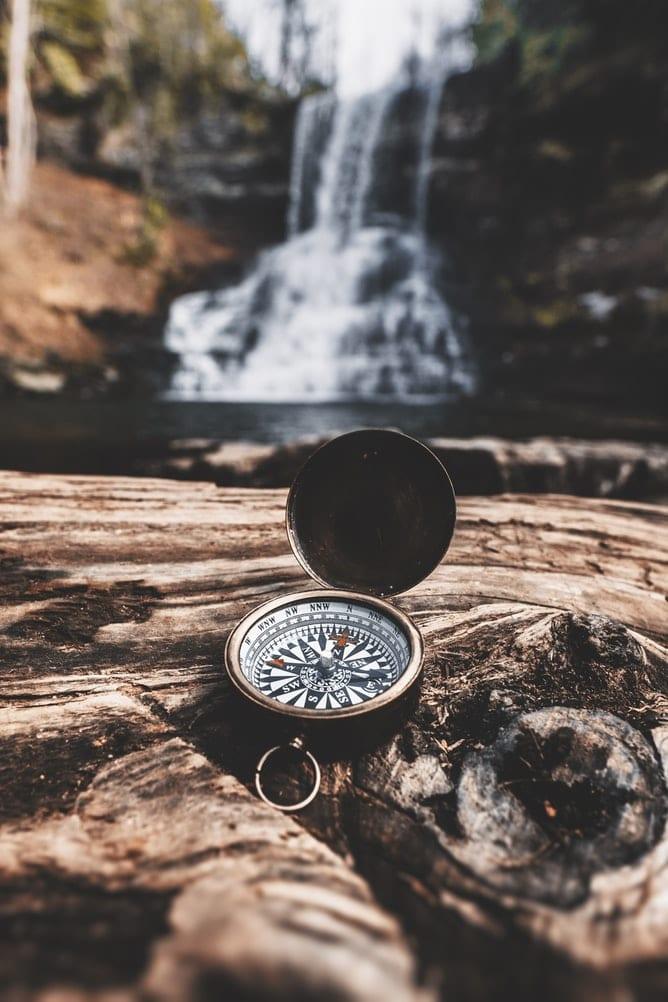 Sivuston navigaatioa kuvastaa kuva kompassista vesiputouksen edessä