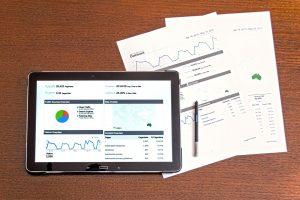 Kuvassa tabletti, josta analytiikkaa auki, Pöydällä myös papereita, joissa myös dataa ja kuvaajia.